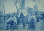 Three sailors on deck of a whaling ship