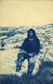 Photograph of an Inuit male seated on rocks