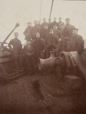 Group of seamen posing behind a winch
