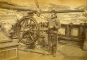 Photograph of bearded sailor in jersy and hat at ship's wheel