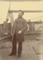 Photograph of Captain Milne with fur hat and beard on deck of ship