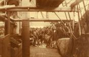Photograph of sailors tidying up the deck after gutting fish