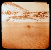 Whaleboat rowing towards land.
