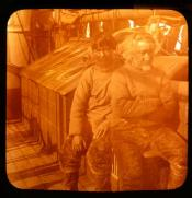 Two Inuit, one of them a pilot, sitting on the deck of a whaling ship