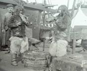 Two Inuit eating whale meat on the deck of a Dundee whaling ship.