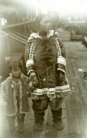Inuit woman holding the hand of a child