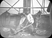 Seaman sitting on deck and splicing a foreganger line onto a harpoon