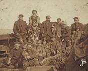 Photograph of a group of sailors and Inuit on deck of ship