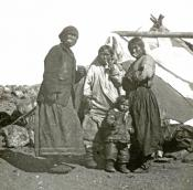 Three Inuit women and one child outside a tent