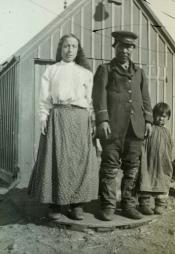 Inuit family standing outside hut