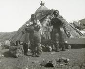 Inuit couple standing outside a tent