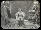 Portrait of Inuit woman sitting on an upturned barrel on the deck of a whaling ship