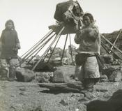 two Inuit standing beside the frame of a tent