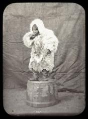 Portrait of an Inuit child standing on an upturned barrel