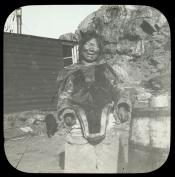Portrait of an Inuit dressed in fur standing in front of a wooden hut