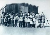 Group of Inuit outside a settlement building