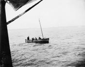 Visitor being rowed out to ship in small boat