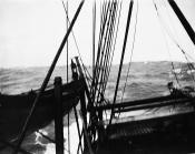 Whale boat on davits alongside whaling ship's deck.
